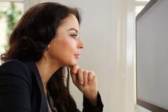 Allvarlig affärskvinna som ser datorskärmen Arkivfoto