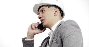 Allvarlig affärsman i en vit konstruktionshjälm som talar på en mobiltelefon på en vit bakgrund arkivfilmer