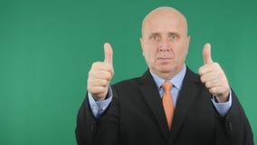 Allvarlig affärsman Make Double Thumbs upp bra gester för en jobbhand royaltyfri bild