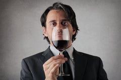 Allvarlig affärsman med ett exponeringsglas av vin Royaltyfri Foto