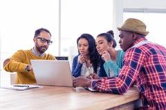 Allvarlig affärsman med kollegor som diskuterar på bärbara datorn arkivfoton