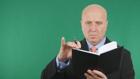 Allvarlig affärsman Reading och handstil i dagordning fotografering för bildbyråer