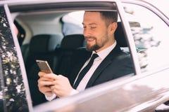 Allvarlig affärsman som använder hans telefon i hans bil som söker efter fönstret arkivbilder