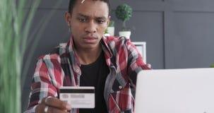 Allvarlig affärsman som använder kreditkorten och bärbara datorn stock video