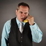 Allvarlig affärsman som talar på banantelefonen royaltyfri bild
