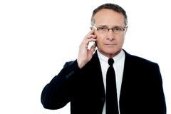 Allvarlig affärsman som talar på telefonen Arkivbild