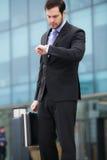 Allvarlig affärsman som waching hans klocka royaltyfri foto