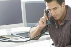 Allvarlig affärsman Using Landline Phone på skrivbordet arkivbild