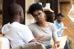 Allvarlig afrikansk amerikankvinna som talar med mannen i kafé arkivbilder