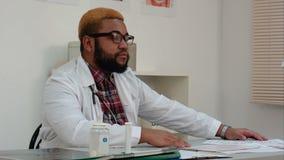 Allvarlig afro amerikansk manlig doktor som lyssnar till patienten stock video