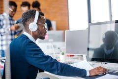 Allvarlig afro- student med hörlurar som förbereder sig för seminarium royaltyfri foto