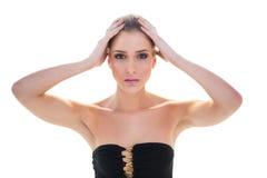 Allvarlig attraktiv blond modell som rymmer hennes huvud royaltyfri bild
