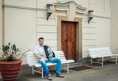 Allvarlig attraktiv brunettman - turist som sitter på bänken royaltyfri bild