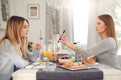 Allvarlig attraktiv ung kvinna som visar hennes bästa vän hennes mobiltelefon Arkivfoto