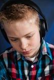 Allvarlig bärande hörlurar för tonårs- pojke Royaltyfri Foto