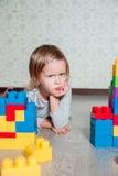 Allvarlig barnflicka som ligger nära ljusa plast- konstruktionskvarter Litet barn som spelar på golvet Framkallande leksaker tidi Arkivfoton