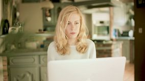Allvarlig blond kvinna som skriver på hennes bärbar dator arkivfilmer