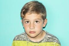 Allvarlig blond pojke med blå bakgrund arkivbilder