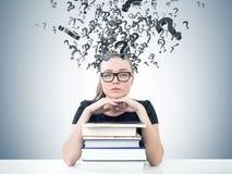 Allvarlig blond student, böcker, frågemarkss royaltyfria bilder