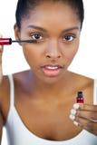 Allvarlig brunett genom att använda mascara för hennes ögonfrans Royaltyfri Fotografi