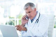Allvarlig doktor som arbetar på bärbara datorn och har påringning arkivfoto