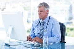 Allvarlig doktor som arbetar på datoren på hans skrivbord Royaltyfria Bilder