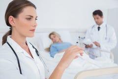 Allvarlig doktor som rymmer en injektionsspruta Royaltyfri Foto