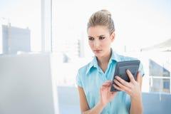 Allvarlig elegant kvinna som använder räknemaskinen som ser bärbara datorn Arkivbild