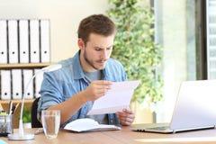 Allvarlig entreprenör som läser ett brev fotografering för bildbyråer
