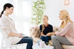 Allvarlig erfaren psykolog som lyssnar till hennes patienter Arkivbilder