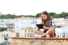 Allvarlig flicka som använder en minnestavla som sitter på en avsats arkivfoton