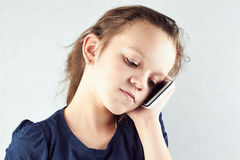 Allvarlig flicka som talar på hennes mobiltelefon Arkivfoton
