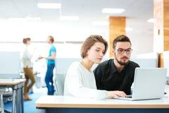 Allvarlig fokuserad man och kvinna som i regeringsställning arbetar med bärbara datorn royaltyfria foton