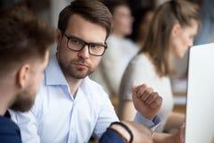 Allvarlig fokuserad manlig anställd som lyssnar till kollegan royaltyfri fotografi