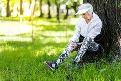 Allvarlig gammal kvinna som skapar på nytt, når utbildning i grön skog fotografering för bildbyråer