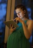 Allvarlig gravid kvinna som hemma använder minnestavlan Arkivbilder