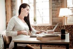 Allvarlig gravid ung kvinna som gör hennes jobb arkivbilder