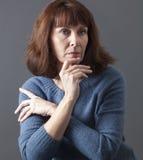 Allvarlig härlig 50-talkvinna som ser tankfull Royaltyfria Bilder