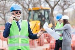 Allvarlig hög arkitekt eller affärsman som talar på telefonen, medan arbeta på en konstruktionsplats royaltyfri fotografi