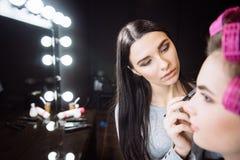 Allvarlig koncentrerad makeupkonstnär som är involverad i hennes arbete Royaltyfri Fotografi