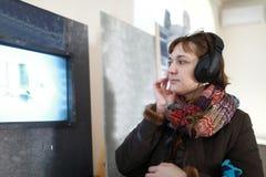 Allvarlig kvinna i hörlurar som håller ögonen på film arkivbild