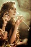 Allvarlig kvinna med drink- och pokerchipen som spelar poker arkivfoton