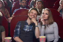 Allvarlig kvinna och le hållande ögonen på film för man på den moderna bion fotografering för bildbyråer