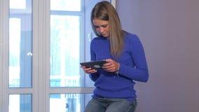 Allvarlig kvinna som använder den digitala minnestavlan, medan sitta på resväskan i hotelllobbyen lager videofilmer