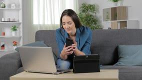 Allvarlig kvinna som hemma använder åtskilliga apparater arkivfilmer