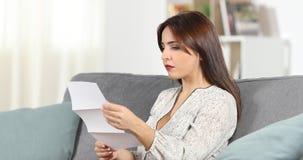 Allvarlig kvinna som hemma läser ett brev stock video