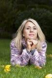 Allvarlig kvinna som ligger i gräs Fotografering för Bildbyråer