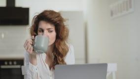 Allvarlig kvinna som ser bärbar datordatoren på öppet kök arkivfilmer