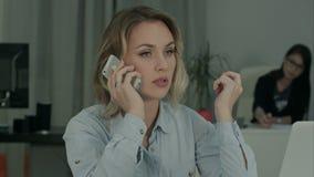 Allvarlig kvinna som ser bärbar datorskärmen, medan tala på telefonen lager videofilmer