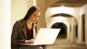 Allvarlig kvinna som skriver på en bärbar dator i natten arkivfilmer